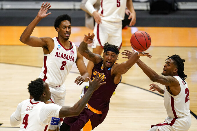 Alabama's Juwan Gary (4), Jordan Bruner (2) and John Petty Jr. (23) force a turn over by Iona guard Isaiah Ross (20) in the first half of a first-round game in the NCAA men's college basketball tournament at Hinkle Fieldhouse in Indianapolis, Saturday, March 20, 2021. (AP Photo/Michael Conroy)