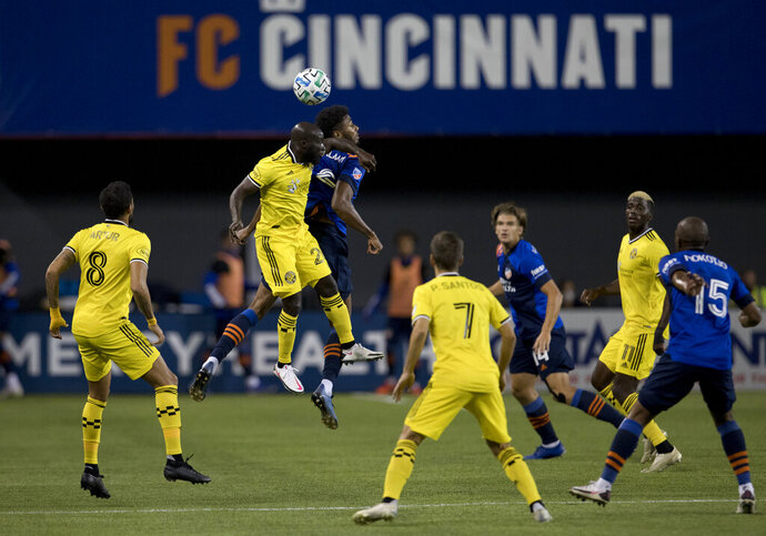 Columbus Crew midfielder Emmanuel Boateng, left, battles for a head ball with FC Cincinnati defender Saad Abdul-Salaam (12)  during the first half of an MLS soccer match Wednesday, Oct. 14, 2020, in Cincinnati. (Albert Cesare/The Cincinnati Enquirer via AP)