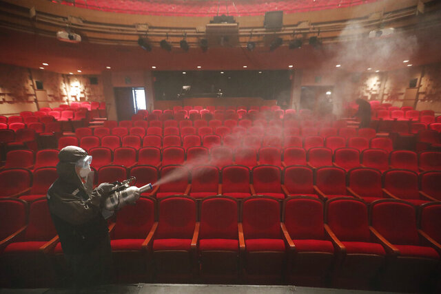 A worker wearing a protective gear sprays disinfectant as a precaution against a new coronavirus at a theater in Sejong Center in Seoul, South Korea, Tuesday, July 21, 2020. South Korea's new virus cases have bounced back Tuesday, a day after it reported its smallest daily jump in local COVID-19 transmissions in two months. (AP Photo/Ahn Young-joon)