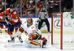 The puck gets past Calgary Flames goaltender David Rittich (33) on a goal by Florida Panthers' Evgenii Dadonov, not seen, as Aleksander Barkov (16) watches during the second period of an NHL hockey game, Friday, Jan. 12, 2018, in Sunrise, Fla. (AP Photo/Lynne Sladky)