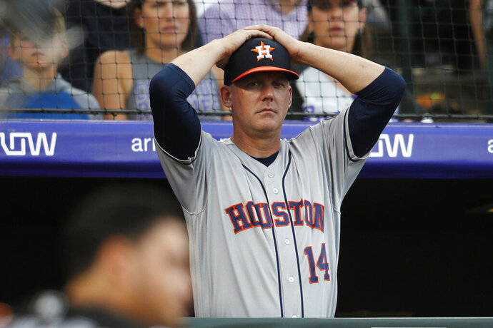 FILE - In this July 2, 2019, file photo, Houston Astros manager AJ Hinch reacts during a baseball game against the Colorado Rockies, in Denver. Houston  manager AJ Hinch and general manager Jeff Luhnow were suspended for the entire season Monday, Jan. 13, 2020,  and the team was fined $5 million for sign-stealing by the team in 2017 and 2018 season. Commissioner Rob Manfred announced the discipline and strongly hinted that current Boston manager Alex Cora — the Astros bench coach in 2017 — will face punishment later. Manfred said Cora developed the sign-stealing system used by the Astros. (AP Photo/David Zalubowski, File)