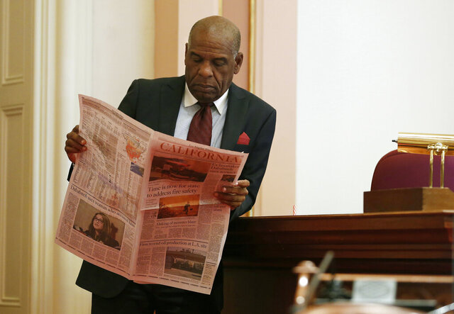 FILE - In this Aug. 16, 2018 file photo, state Sen. Steven Bradford, D-Gardena, looks over a newspaper during a break in the Senate session, in Sacramento, Calif. Sen. Patricia Bates, R-Laguna Niguel, announced Thursday, Jan. 23, 2020 that she has introduced legislation exempting freelance writers and newspaper carriers from a broad new California law requiring that many be treated as employees rather than independent contractors. (AP Photo/Rich Pedroncelli, File)