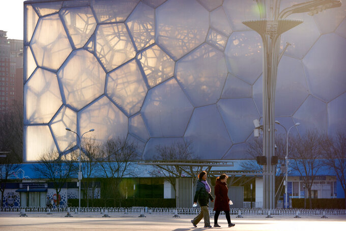 """People walk past the Water Cube, which will be known as the Ice Cube when it hosts events for the 2022 Beijing Winter Olympics, in Beijing, Tuesday, Feb. 2, 2021. The 2022 Beijing Winter Olympics will open a year from now. Most of the venues have been completed as the Chinese capital becomes the first city to hold both the Winter and Summer Olympics. Beijing held the 2008 Summer Olympics. But these Olympics are presenting some major problems. They are already scarred by accusations of rights abuses including """"genocide""""against more than 1 million Uighurs and other Muslim ethnic groups in western China. (AP Photo/Mark Schiefelbein)"""