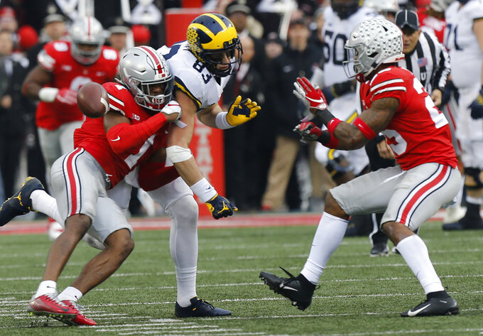 Ohio State defensive backs Jeffrey Okudah, left, and Brendon White, right, break up a pass intended for Michigan tight end Zach Gentry during the second half of an NCAA college football game Saturday, Nov. 24, 2018, in Columbus, Ohio. Ohio State beat Michigan 62-39. (AP Photo/Jay LaPrete)