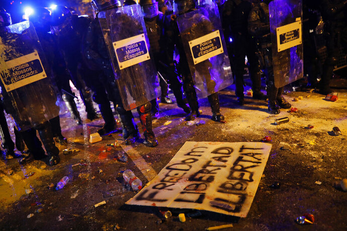 A poster lies on the ground during clashes between protestors and riot police outside the Spanish Government Office in Barcelona, Spain, Tuesday, Oct. 15, 2019. Spain's Supreme Court on Monday convicted 12 former Catalan politicians and activists for their roles in a secession bid in 2017, a ruling that immediately inflamed independence supporters in the wealthy northeastern region. (AP Photo/Bernat Armangue)