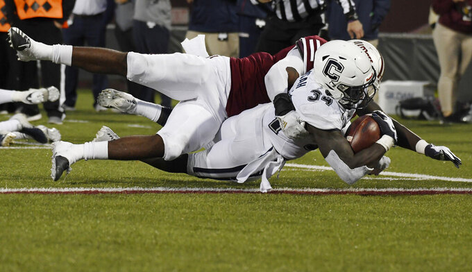 Connecticut running back Kevin Mensah (34) scores a touchdown as he is tackled by Massachusetts linebacker Jarvis Miller (2) during the second half of an NCAA college football game, Saturday, Oct. 26,, 2019, in Amherst, Mass. (AP Photo/Jessica Hill)