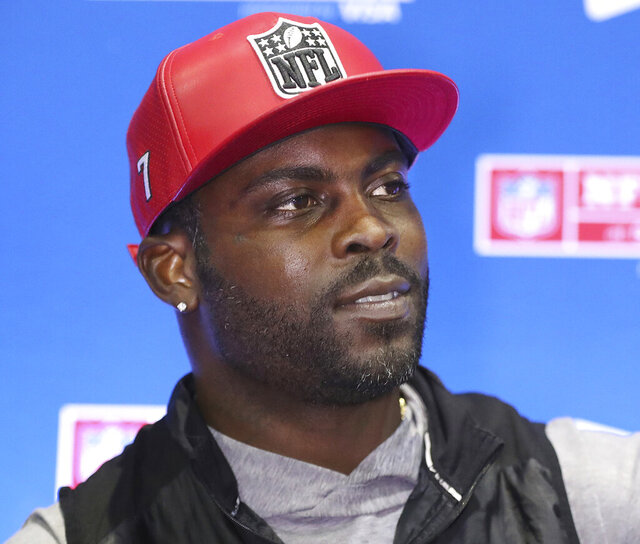 File-This jan. 31, 2019, file photo shows former Falcons and Eagles quarterback Michael Vick wearing one of his special edition New Era #7 hats while signing autographs in the NFL Shop at the Super Bowl Experience in Atlanta. The Virginia city of Hampton, says Vick owes $70K in unpaid taxes. (Curtis Compton/Atlanta Journal-Constitution via AP, File)