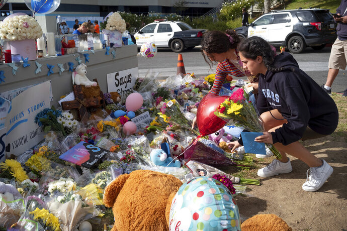 Saugus high students place flowers in front of a growing memorial in front of Saugus high Tuesday, Nov. 19, 2019. Students were allowed back to collect their belongings left behind after the tragic shooting last Thursday. Classes will resume at the high school on Dec. 2. (David Crane/The Orange County Register via AP)