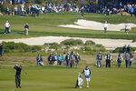 Phil Mickelson, lower left, hits a shot from the sixth fairway of the Monterey Peninsula County Club Shore Course during the second round of the AT&T Pebble Beach National Pro-Am golf tournament Friday, Feb. 7, 2020, in Pebble Beach, Calif. (AP Photo/Tony Avelar)