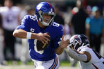 New York Giants quarterback Daniel Jones (8) looks to pass under pressure from Atlanta Falcons defensive tackle Ta'Quon Graham, right, during the second half of an NFL football game, Sunday, Sept. 26, 2021, in East Rutherford, N.J. (AP Photo/Seth Wenig)