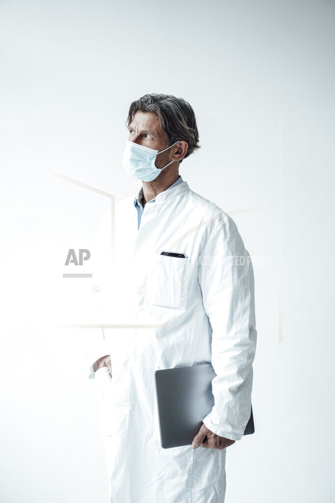 Male healthcare worker standing with hand in pocket in hospital during pandemic