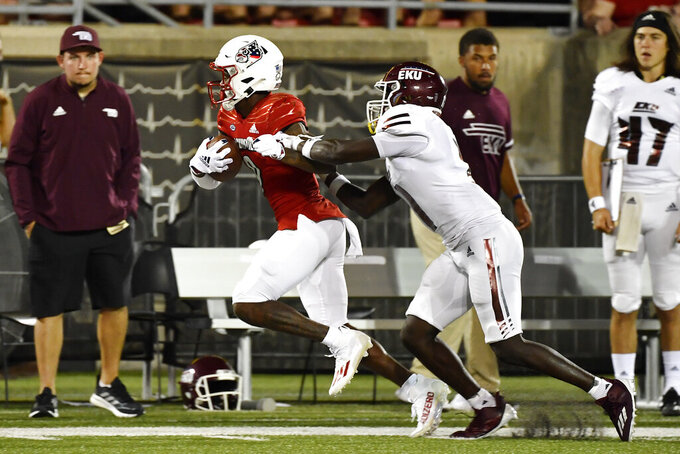 Louisville wide receiver Ahmari Huggins-Bruce, front left, runs from the grasp of Eatern Kentucky defensive back Joseph Sayles, front right, during the second half of an NCAA college football game in Louisville, Ky., Saturday, Sept. 11, 2021. (AP Photo/Timothy D. Easley)