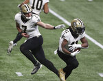 New Orleans Saints quarterback Taysom Hill hands off to running back Alvin Kamara during the first quarter of an NFL football game against the Atlanta Falcons, Sunday, Dec. 6, 2020, in Atlanta. (Curtis Compton/Atlanta Journal-Constitution via AP)