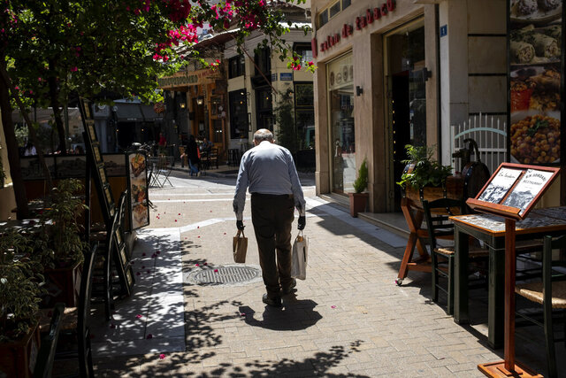 A man carries shopping bags on a pedestrian street, in Athens, on Friday, June 5, 2020. The European Commission says Greece is likely to suffer deepest recession in the eurozone this year, but first quarter growth figures were better than expected. (AP Photo/Yorgos Karahalis)