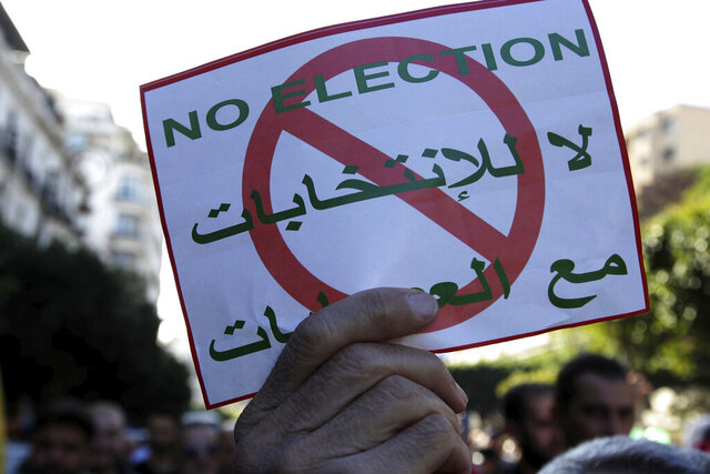 FILE - In this Dec. 6, 2019 file photo, people demonstrate with anti-election posters in Algiers. Algeria's powerful army chief promises that a presidential election on Thursday, Dec. 12, 2019 will define the contours of a new era for a nation where the highest office has stood vacant for eight months. The tenacious pro-democracy movement which forced leader Abdelaziz Bouteflika to resign after 20 years in power doesn't trust the confident claim and is boycotting the vote. (AP Photo/Fateh Guidoum, File)