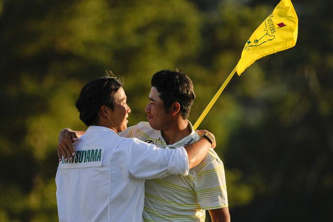 Hideki Matsuyama, of Japan, hugs his caddie Shota Hayafuji after winning the Masters golf tournament on Sunday, April 11, 2021, in Augusta, Ga. (AP Photo/David J. Phillip)