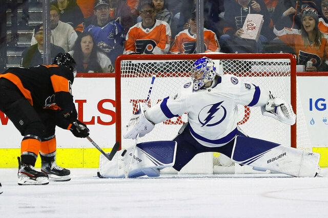 Tampa Bay Lightning's Andrei Vasilevskiy, right, blocks a shot by Philadelphia Flyers' Travis Sanheim during the third period of an NHL hockey game, Saturday, Jan. 11, 2020, in Philadelphia. (AP Photo/Matt Slocum)