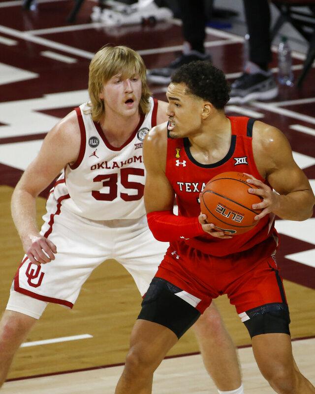 Texas Tech's Marcus Santos-Silva (14) is defended by Oklahoma's Brady Manek (35) during the first half of an NCAA college basketball game in Norman, Okla., Tuesday, Dec. 22, 2020. (AP Photo/Garett Fisbeck)