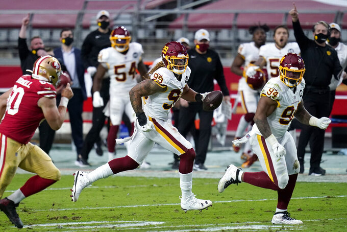 Washington Football Team defensive end Chase Young (99) runs back a fumble recovery for a touchdown against the San Francisco 49ers during the first half of an NFL football game, Sunday, Dec. 13, 2020, in Glendale, Ariz. (AP Photo/Ross D. Franklin)
