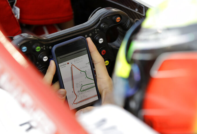 Formula 2 driver Mick Schumacher prepares in the garage of Prema racing team car, during the Formula 2 qualifying session at the Bahrain International Circuit in Sakhir, Bahrain, Friday, March 29, 2019. It promises to be a whirlwind few days for the son of Formula One great Michael Schumacher, as he makes his F2 debut this weekend and then drives in his first F1 test for Ferrari on Tuesday. (AP Photo/Luca Bruno)