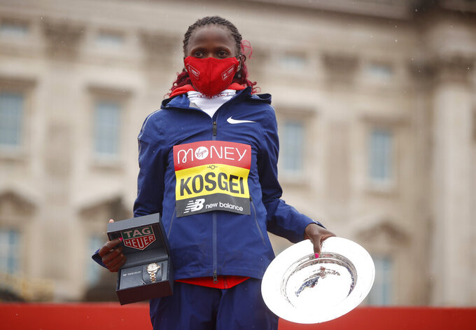 Kenya's Brigid Kosgei celebrates on the podium after winning the London Marathon in London, England, Sunday, Oct. 4, 2020.(John Sibley/Pool via AP)