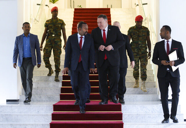 FILE - In this Tuesday, Feb. 18, 2020 file photo, U.S. Secretary of State Mike Pompeo, center right, walks with Ethiopia's Prime Minister Abiy Ahmed, center-left, after meeting at the Prime Minister's office in Addis Ababa. The State Department said Wednesday, Sept. 2, 2020 that on the guidance of President Donald Trump the U.S. is suspending some aid to Ethiopia over the