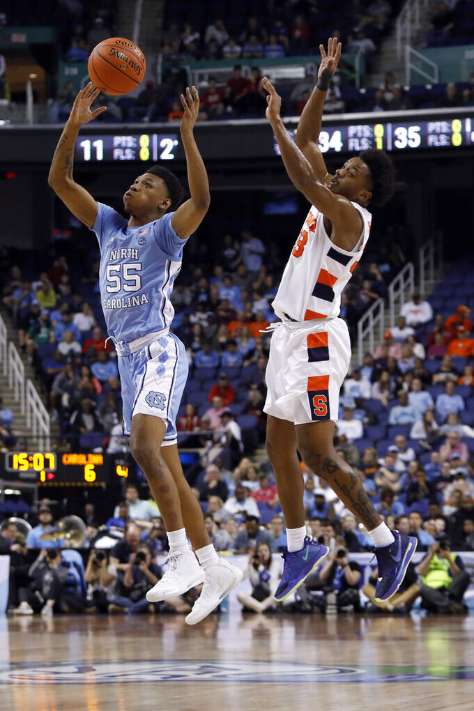 North Carolina guard Christian Keeling (55) and Syracuse forward Elijah Hughes jump for the ball during the first half of an NCAA college basketball game at the Atlantic Coast Conference tournament in Greensboro, N.C., Wednesday, March 11, 2020. (AP Photo/Ben McKeown)