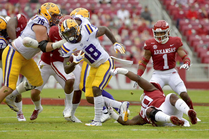 LSU running back Chris Curry (18) spins away from Arkansas defender Marcus Miller (90) during the first half of an NCAA college football game Saturday, Nov. 21, 2020, in Fayetteville, Ark. (AP Photo/Michael Woods)