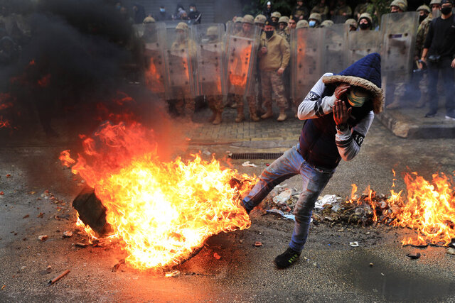 A protester covers himself from flames during a protest against deteriorating living conditions and strict coronavirus lockdown measures, in Tripoli, north Lebanon, Thursday, Jan. 28, 2021. Violent confrontations overnight between protesters and security forces in northern Lebanon left a 30-year-old man dead and more than 220 people injured, the state news agency said Thursday. (AP Photo/Hussein Malla)