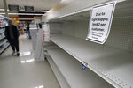 A passer-by walks down an aisle with empty shelves where paper towels are normally on display at a grocery store, Thursday, March 26, 2020, in Quincy, Mass. Paper towels and toilet paper have sold briskly as people take measures to cope with the coronavirus. The new coronavirus causes mild or moderate symptoms for most people, but for some, especially older adults and people with existing health problems, it can cause more severe illness or death. (AP Photo/Steven Senne)