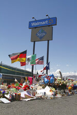 In this Aug. 12, 2019 photo, mourners visit the makeshift memorial near the Walmart in El Paso, Texas, where 22 people were killed in a mass shooting that police are investigating as a terrorist attack targeting Latinos. The flags show the nationalities of those killed in the attack, including a German man who lived in nearby Ciudad Juarez, Mexico. On Thursday, Aug. 22, 2019, Walmart said it plans to reopen the El Paso store where 22 people were killed in a mass shooting, but the entire interior of the building will first be rebuilt. (AP Photo/Cedar Attanasio)
