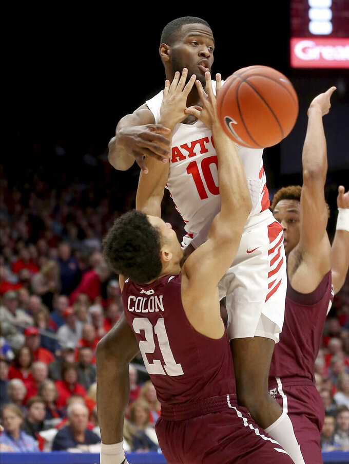 Dayton's Jalen Crutcher (10) passes the ball as he drives to the basket against Fordham's Josh Colon (21) during the first half of an NCAA college basketball game Saturday, Feb. 1, 2020, in Dayton, Ohio. (AP Photo/Tony Tribble)