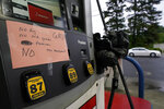 A hand written sign is posted on a gas pump, showing that the service station is out of all grades of fuel Wednesday, May 12, 2021, in Charlotte, N.C.  Several gas stations in the Southeast reported running out of fuel, primarily because of what analysts say is unwarranted panic-buying among drivers, as the shutdown of a major pipeline by hackers entered its fifth day.  (AP Photo/Chris Carlson)