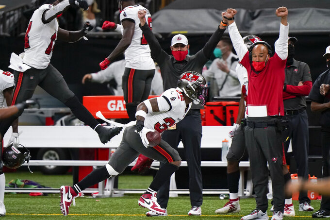 Tampa Bay Buccaneers players and coaches celebrate on the sideline as safety Mike Edwards (32) runs after he intercepted a pass against the New Orleans Saints during the second half of an NFL divisional round playoff football game, Sunday, Jan. 17, 2021, in New Orleans. (AP Photo/Brynn Anderson)