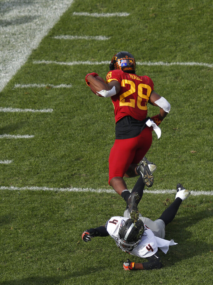 Oklahoma State cornerback A.J. Green, bottom, trips up Iowa State running back Breece Hall during the first half of an NCAA college football game, Saturday, Oct. 26, 2019, in Ames, Iowa. (AP Photo/Matthew Putney)