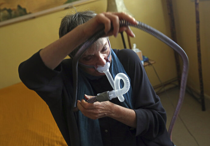 Joelle Dobrow demonstrates how she puts on her sleep apnea breathing device at her home in Los Angeles Thursday, July 12, 2018. It's been two decades since doctors fully recognized that breathing that stops and starts during sleep is tied to a host of health issues, even early death, but there still isn't a treatment that most people find easy to use. Dobrow said it took her seven years to find one she liked.
