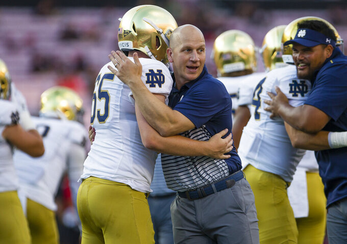 Notre Dame defensive coordinator Clark Lea hugs Notre Dame's Michael Vinson (65) before an NCAA college football game against Louisville, in Louisville, Ky., in this Monday, Sept. 2, 2019, file photo. Vanderbilt is negotiating a deal with Notre Dame defensive coordinator Clark Lea to make the former Commodores player its new head coach. Two people with knowledge of the situation told The Associated Press details of a contract were still being worked out but Lea was the school's top choice. (Michael Caterina/South Bend Tribune via AP)