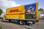 A DHL delivery truck passes a DHL location Tuesday, Oct. 20, 2020, in New York. DHL' eCommerce Solutions, a division that specializes in small packages for mid-size shippers, is hiring 900 more permanent workers to its current labor force of 3,000. It also will hire 1,400 temporary workers. (AP Photo/Frank Franklin II)