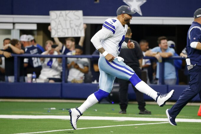 Dallas Cowboys quarterback Dak Prescott (4) runs off the field after the team's NFL football game against the Carolina Panthers in Arlington, Texas, Sunday, Oct. 3, 2021. (AP Photo/Michael Ainsworth)