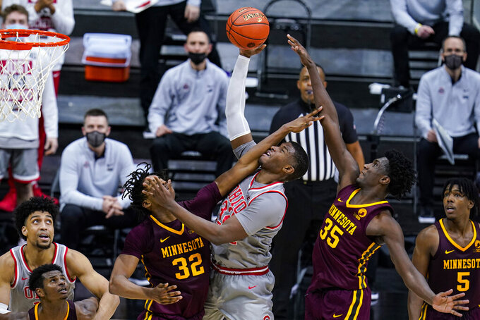 Ohio State forward E.J. Liddell (32) shoots between Minnesota center Sam Freeman (32) and forward Isaiah Ihnen (35) in the second half of an NCAA college basketball game at the Big Ten Conference tournament in Indianapolis, Thursday, March 11, 2021. (AP Photo/Michael Conroy)