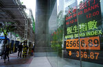 People walk past an electronic board showing Hong Kong share index outside a local bank in Hong Kong, Monday, Dec. 10, 2018. Asian markets were broadly lower Monday after China protested the arrest of a senior executive of Chinese electronics giant Huawei, who is suspected of trying to evade U.S. trade curbs on Iran. (AP Photo/Vincent Yu)