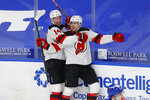 New Jersey Devils forward Michael McLeod (20) celebrates his goal with teammate forward Nathan Bastian (14) during the third period of an NHL hockey game against the Buffalo Sabres, Sunday, Jan. 31, 2021, in Buffalo, N.Y. (AP Photo/Jeffrey T. Barnes)