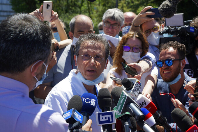 """Dr. Sabino Scolletta talks to the media outside the Santa Maria alle Scotte hospital as they wait for a medical bulletin on Alex Zanardi, in Siena, Italy, Saturday, June 20, 2020. Italian race car champion-turned-Paralympic gold medalist Alex Zanardi remains in serious condition a day after crashing his handbike into a truck and smashing his face. A medical bulletin from the Santa Maria alle Scotte hospital in Siena says that Zanardi is hooked up to an artificial ventilator and has """"stable"""" blood flow while his neurological status """"remains serious."""" Zanardi was transported by helicopter to the hospital after crashing near the Tuscan town of Pienza during a relay race Friday.  (Alessandro La Rocca/LaPresse via AP)"""