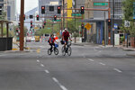 A pair of cyclists navigate an empty one-way street in downtown Phoenix Wednesday, April 1, 2020 during the first full day of Arizona Gov. Doug Ducey's stay-at-home order to slow the spread of the new coronavirus. Gov. Ducey is urging Arizonans to be understanding and reasonable as people and businesses face April 1 due dates for bills such as mortgages, rent, utilities and internet service since the COVID-19 coronavirus outbreak has slowed the economy. The new coronavirus causes mild or moderate symptoms for most people, but for some, especially older adults and people with existing health problems, it can cause more severe illness or death. (AP Photo/Matt York)