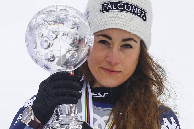 Italy's Sofia Goggia poses with the trophy of the alpine ski, women's World Cup downhill, in Lenzerheide, Switzerland, Wednesday, March 17, 2021. (AP Photo/Marco Trovati)