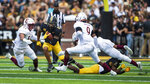 Appalachian State's Jalen Virgil runs the ball while closely defended by Elon's Nick Veloz (54) and Shamari Wingrd (9) during the second quarter of an NCAA college football game, Saturday, Sept. 18, 2021, at Kidd Brewer Stadium in Boone, N.C. (Kenneth Ferriera/News & Record via AP)