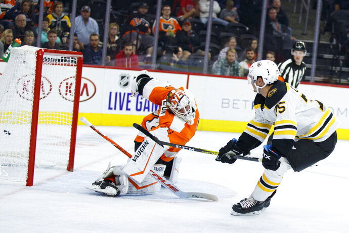 Boston Bruins' Connor Clifton, right, scores a goal past Philadelphia Flyers' Alex Lyon during the third period of a preseason NHL hockey game Thursday, Sept. 19, 2019, in Philadelphia. (AP Photo/Matt Slocum)