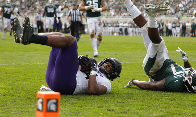 Northwestern's Cameron Green, left, comes down with a touchdown against Michigan State's Tyriq Thompson during the third quarter of an NCAA college football game, Saturday, Oct. 6, 2018, in East Lansing, Mich. Northwestern won 29-19. (AP Photo/Al Goldis)