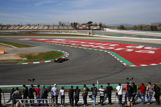 Motor racing fans watch as a Ferrari takes a curve during a Formula One pre-season testing session at the Catalunya racetrack in Montmelo, outside Barcelona, Spain, Tuesday, Feb. 26, 2019. (AP Photo/Joan Monfort)