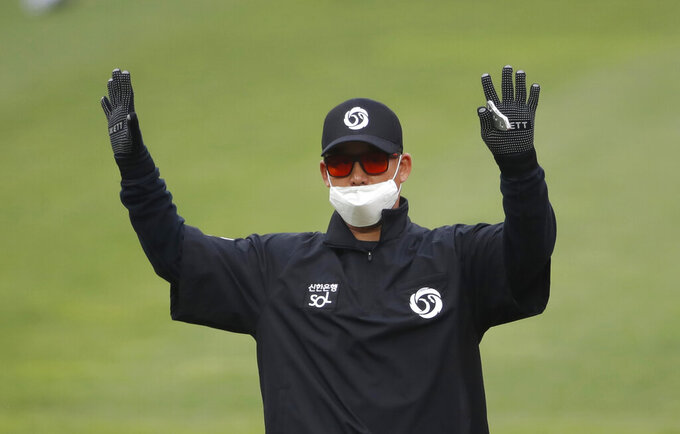 Second base umpire Kim Jun-hee wearing a mask and gloves as a precaution against the new coronavirus calls during a baseball game between Hanwha Eagles and SK Wyverns in Incheon, South Korea, Tuesday, May 5, 2020. With umpires fitted with masks and cheerleaders dancing beneath vast rows of empty seats, a new baseball season got underway in South Korea following a weeks-long delay because of the coronavirus pandemic.(AP Photo/Lee Jin-man)